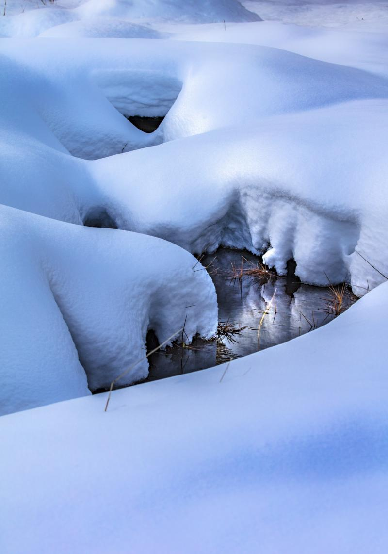 Close up pillows smooth shapes. - The water winding through the smooth shapes made by fresh snow